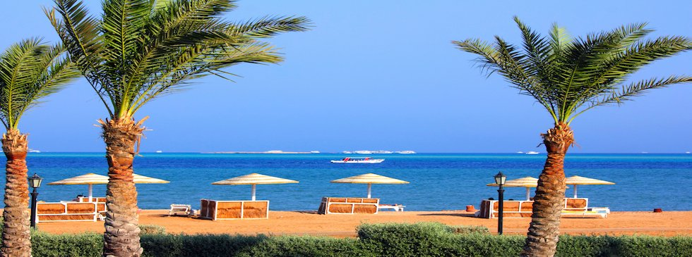 El Gouna sea side view with sandy beach, blue sea water and green palm trees