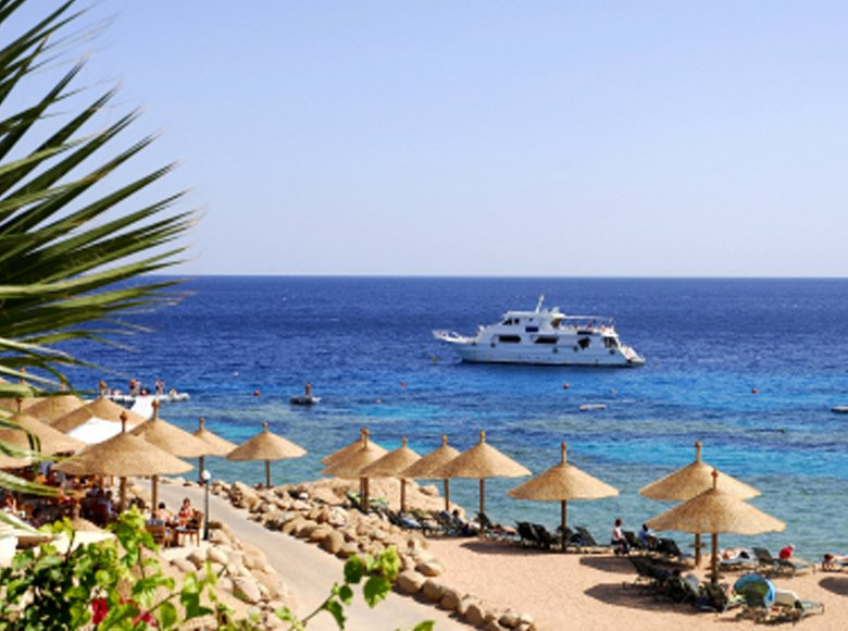 Red Sea beach in Egypt with cruise and tourists enjoying the sea view