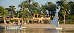 Karnak Resort Riverside view with a yacht and a motor boat